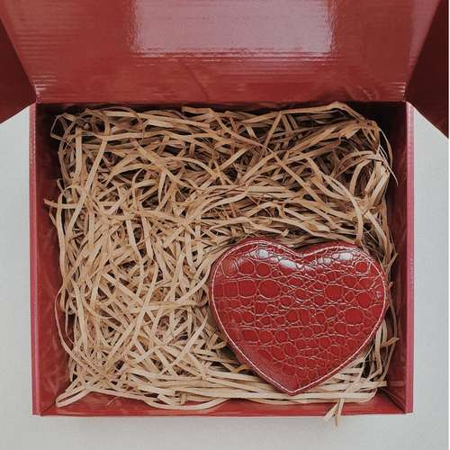 Red gift box filled with brown shredded paper. On the bottom right is a dark red heart shape crocodile skin jewelry case.