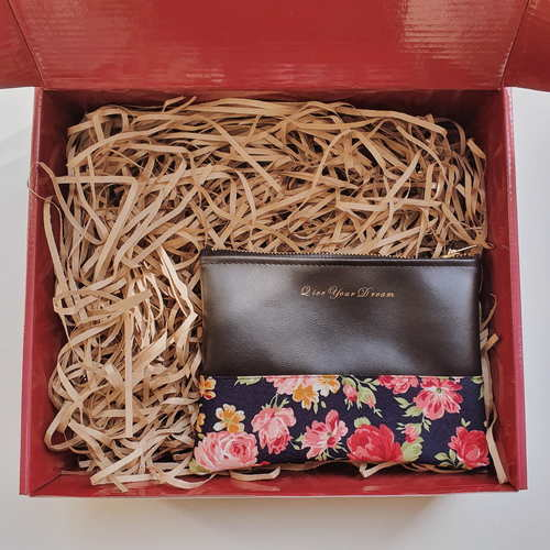 Red gift box filled with brown shredded paper. On the bottom half is a black leather clutch with the quote Live your dream in gold. The clutch has floral prints on the bottom half and gold zipper.