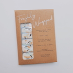 A brown rectangle paper packaging of a nail wrap. The nail wrap has five different design for each finger nail. The nail wrap has a nude-coloured base with strokes in coral, light green and black. The words Freshly Wrapped can be seen on top of the packaging.
