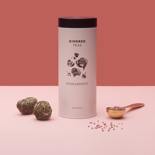 A pale pink cylindrical tin can with black lid. The tin can is labeled Kindred Teas on top, with flowers in the middle and the words Endearment and 8 blooms below.